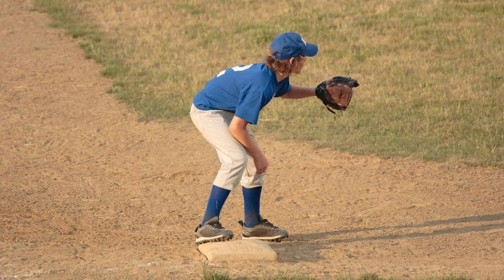 A third baseman wearing blue getting ready for the pitch